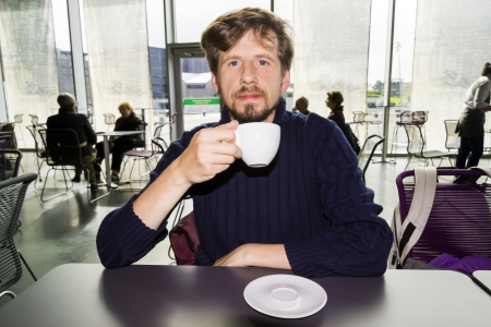 Young man drinking coffeein a cafe photo