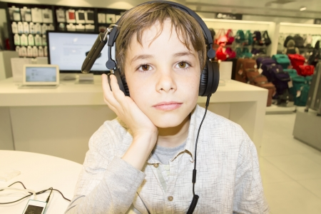 Portrait of a sweet young boy listening to music on headphones Stock Photo - 24514888