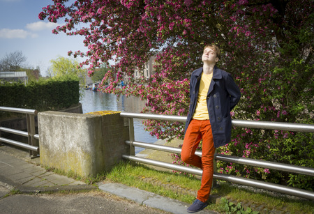 Young attractive stylish blond man against canal . photo