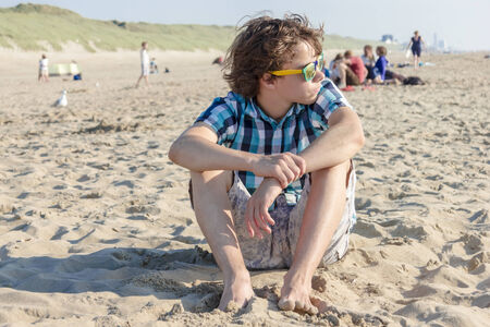 Portrait of  teenage guy siting on sand photo