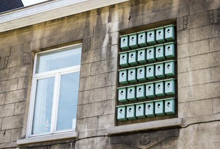bilding: Facade of bilding with birdhouses in window  in Ghent, Belgium