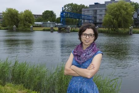 Portrait der jungen Frau im blauen Kleid gegen einen holländischen Kanal Standard-Bild