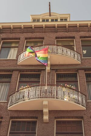 Gay Pride Rainbow Flag in a Street in historical city center of Amsterdam. It is one of the most romantic and beautiful cities in Europe. Foto de archivo - 130817009