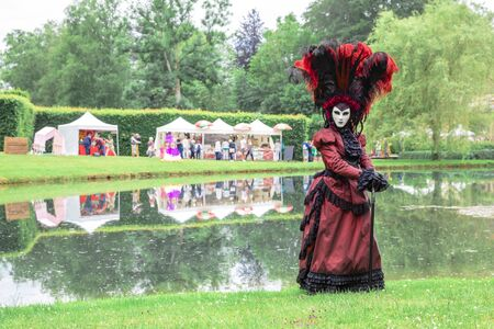 Woman in a traditional Venetian carnival costume and mask against a park background. Stok Fotoğraf