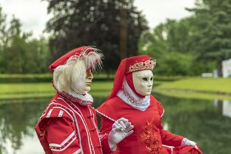 Couple standing in masks and red masquerade costumes during Venetian carnival in Annevoie gardens, Rue des jardins, 37 a, Annevoie/ Belgium