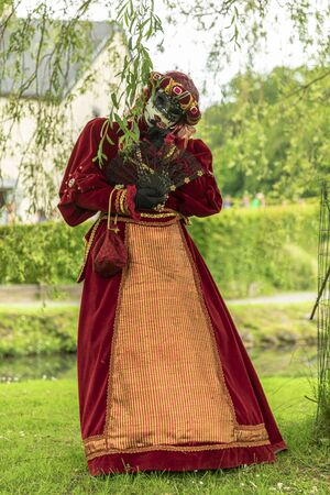 A woman acting in a venetian mask and red masquerade costume in a park