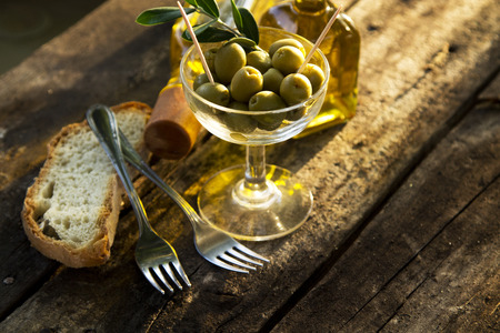 olives and bottles of oil with slice of bread on vintage wood