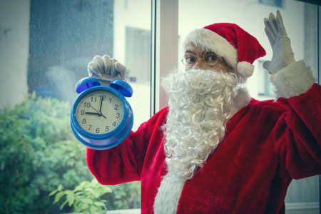santa claus with alarm clock at christmas and surprise expression Archivio Fotografico