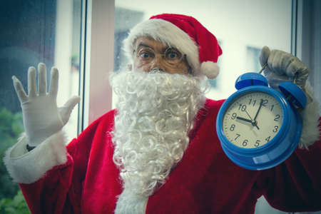 santa claus with alarm clock at christmas and surprise expression