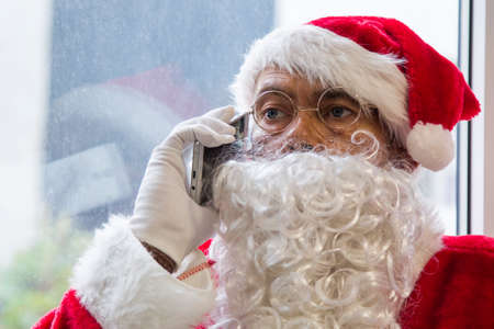 happy santa claus talking with mobile phone at christmas