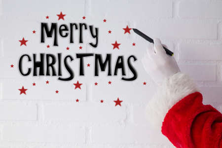 Santa Claus writing Christmas greeting with the pen on the white brick wall 写真素材