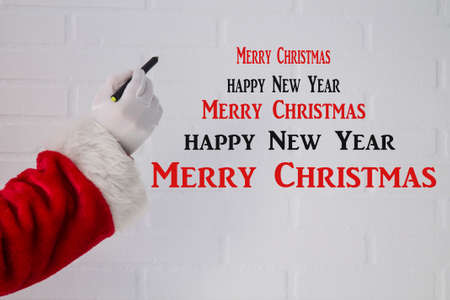 Santa Claus writing Christmas and New Year's congratulations with the pen