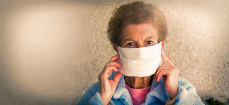 portrait of senior woman with disposable medical mask. Safety in public places during coronavirus outbreak.
