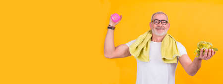 attractive senior man with measuring tape and dumbbells