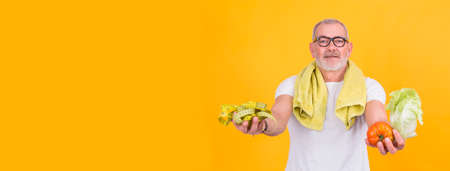 attractive mature man with tape measure in one hand and lettuce and tomato in the other, diet and health concept