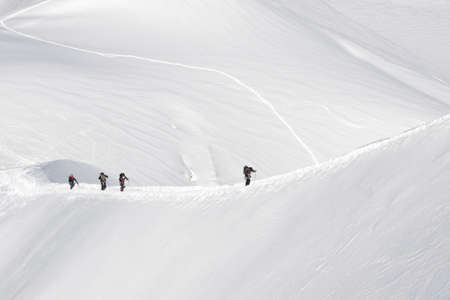 four people climbing on a ridgein the snow photo