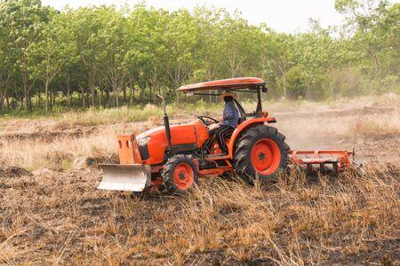 stubble field: Farmer plowing stubble field with orange tractor