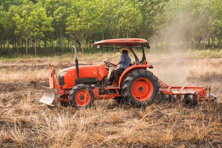 arando: Farmer plowing stubble field with orange tractor