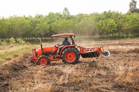 arando: Agricultor arando campo de rastrojos con el tractor de naranja Foto de archivo