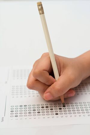 filling in: womans hands filling in standardized test form