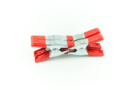 Metal spring clamp with red plastic isolated on white Stock Photo