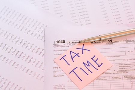 cpa: Tax Time written on pink sticker note with on U.S. tax form