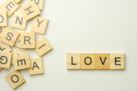 Text wooden blocks spelling the word LOVE on white background Фото со стока