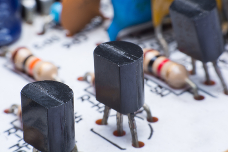 Closeup electronic hardware. transistor on the white circuit board