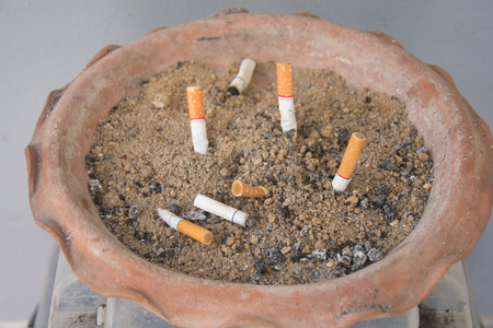 The rest of cigarettes in the ashtray. There are many types of cigarette stub on the sand in the ashtray.