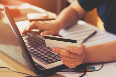 女性手ラップトップ コンピューターを使用し、クレジット カードを保持します。オンライン ショッピングの概念