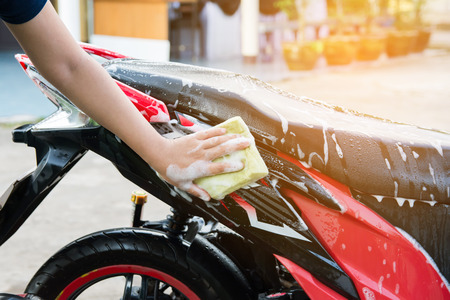 motorfiets schoon, vrouwelijke hand met gele schuim spons wassen van een motorfiets. Stockfoto
