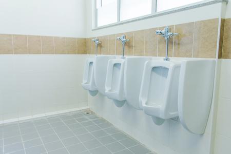 row of urinals men public toilet, Closeup white urinals in mens bathroom, design of white ceramic urinals for men in toilet room.