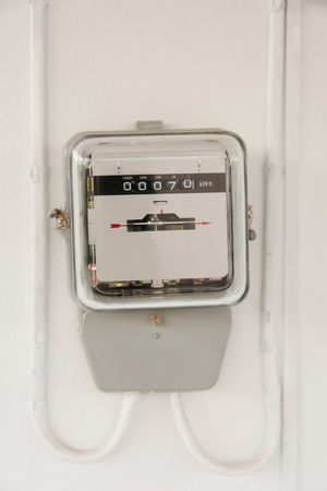 Analog electric meter on cement wall. Electricity consumption concept. Stock Photo