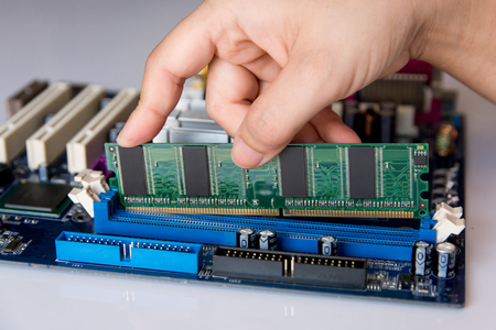 Technician installing RAM stick (random access memory) to socket on motherboard Foto de archivo
