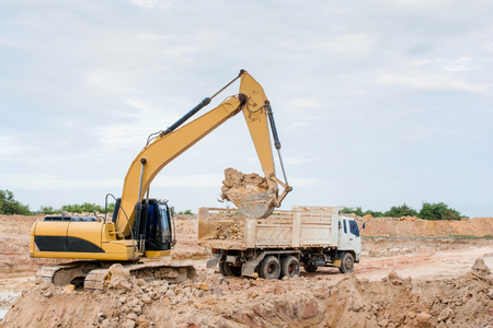 Yellow excavator machine loading soil into a dump truck at construction site Stock Photo