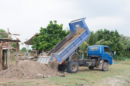 Blue dump truck unloading soil at construction site