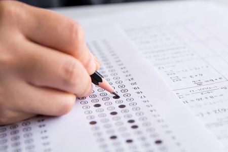 Schülerhand hält Bleistift und wählt ausgewählte Auswahl auf Antwortbögen und Mathematik-Fragebögen. Studenten testen die Prüfung. Schulprüfung