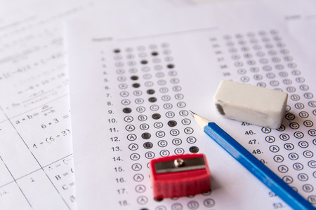 Pencil, Sharpener and eraser on answer sheets or Standardized test form with answers bubbled. multiple choice answer sheet