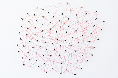 Linking entities, social media, Communications Network, The connection between the two networks. Network simulation on white paper linked together created by black nail and red thread Stock fotó