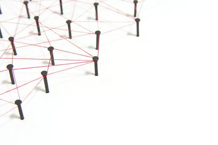 Verknüpfung von Entitäten, sozialen Medien, Kommunikationsnetzwerk, Die Verbindung zwischen den beiden Netzwerken. Netzwerksimulation auf weißem Papier, das durch schwarzen Nagel und roten Faden miteinander verbunden ist