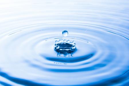 Water drop falling into water make waves. Water splash or water drop background. Stockfoto