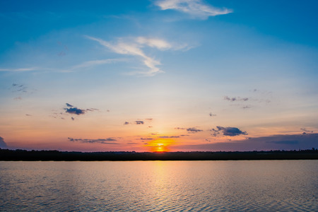 Sunset in the lake. beautiful sunset behind the clouds above the over lake landscape background. dramatic sky with cloud at sunset