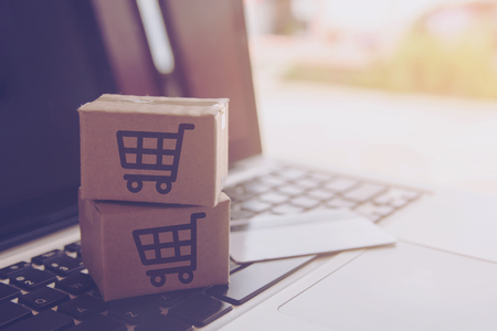 Shopping online concept - Shopping service on The online web. with payment by credit card and offers home delivery. parcel or Paper cartons with a shopping cart logo on a laptop keyboard Archivio Fotografico
