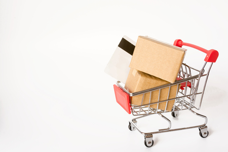 Shopping concept : Cartons or Paper boxes and credit card in red shopping cart on white background. online shopping consumers can shop from home and delivery service. with copy space