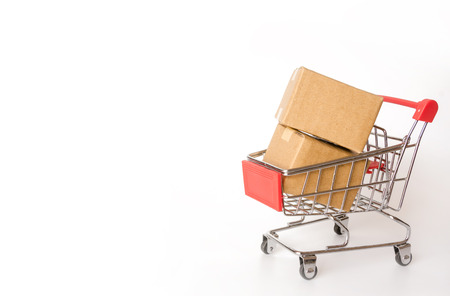 Shopping concept : Cartons or Paper boxes in red shopping cart on white background. online shopping consumers can shop from home and delivery service. with copy space