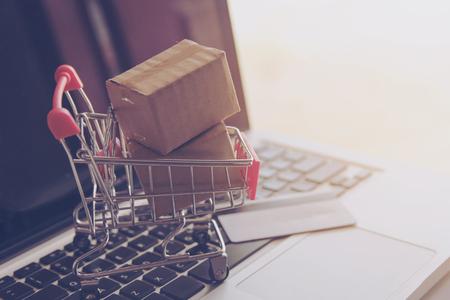 Concetto di acquisto online - Servizio di acquisto sul web online. con pagamento con carta di credito e offre la consegna a domicilio. pacchi o cartoni di carta con il logo del carrello della spesa sulla tastiera di un laptop
