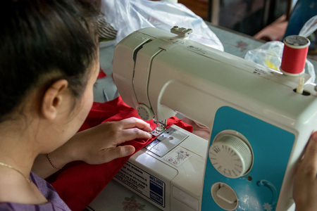 Woman seamstress working making clothes on a sewing machine.
