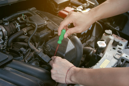Car mechanic working with screwdriver in garage. Repair service. Stock Photo