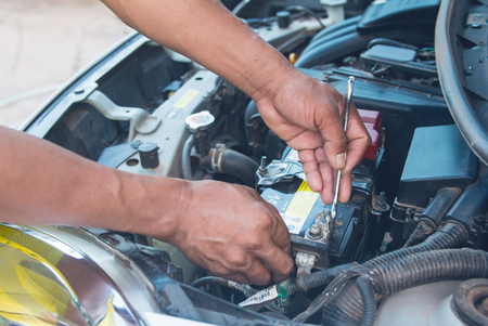 Car mechanic working Install battery with wrench in garage. Repair service. Stock Photo