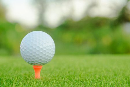 Golf ball with orange tee on green grass ready to play at golf course. with copy space